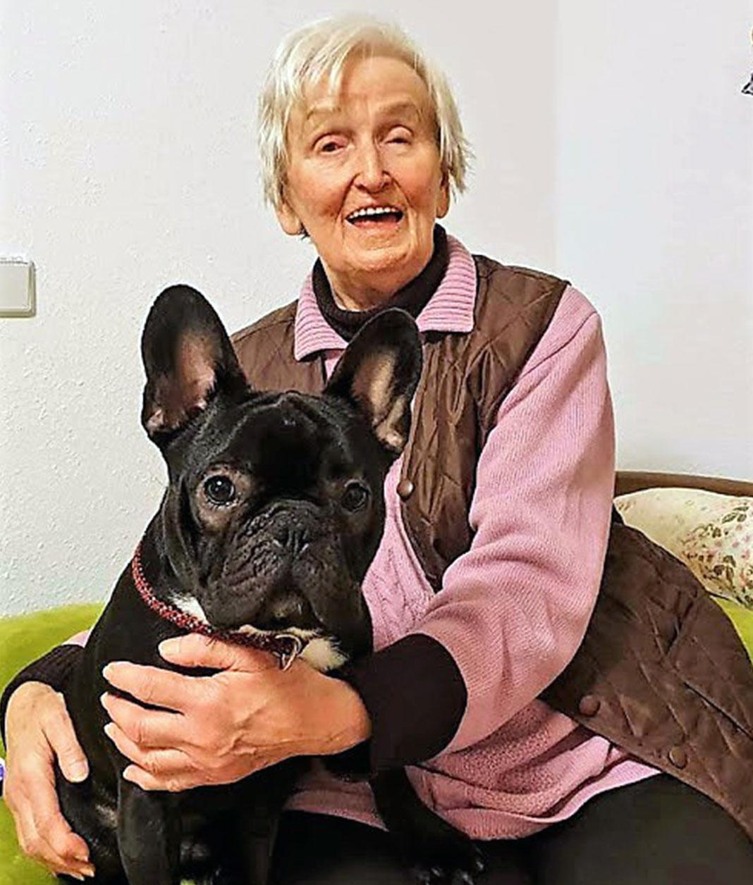 Mitbewohner hält einen Hund im Arm